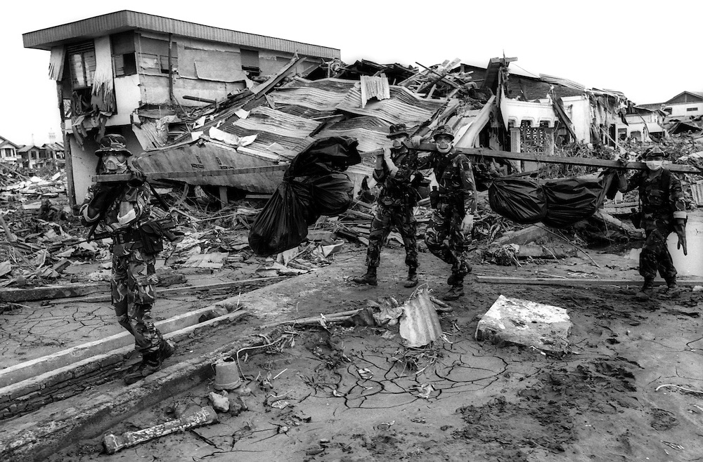 Members of Indonesia's armed forces, TNI, collect bodies from the Tsunami affected wreckage that was Banda Aceh. Indonesia.