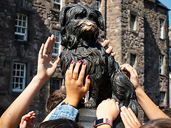 Tourists touch statue of Greyfriars Bobby in Old Town of Edinburgh, Scotland, UK
