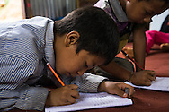 Aakash Tamang, 9, writes lines with a pencil in his notebook in the SOS Children's Villages Child Care Space in Rayale, Nepal on 1 July 2015. Aakash Tamang's house had collapsed during the earthquake on 25th April 2015. Fortunately, all his family members are safe, but they are now displaced. Aakash has been very fond of the Child Care Space, where he enjoys learning, doing drama plays, and dancing with his friends. Photo by Suzanne Lee for SOS Children's Villages