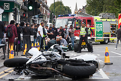 London, August 24th 2014. Paramedics and firefighters attend to an injured biker who appeared to have run into the back of a car at the intersection of Chamberlayne Road and Harvist Road in Kensal Green. A number of bikers had been roaring up and down the road as day one of the Notting Hill Carnival came to a close.