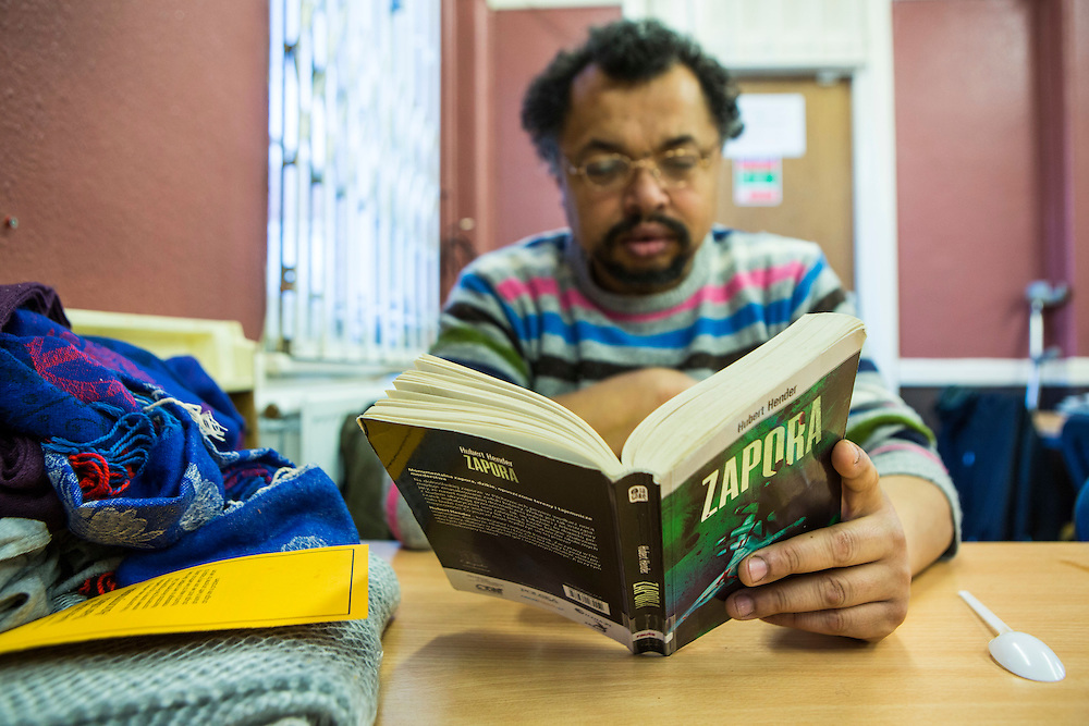 A Polish man sits reading his book in the dining room of Slough Homeless our concern (SHOC) A local homeless charity helping the homeless and vulnerable in Slough. Berkshire, UK.