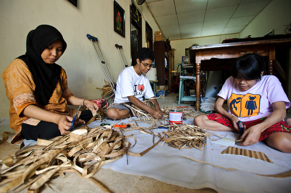Disabled processing dried water hyacinth stems for use as a material to make sandals, Makassar, Sulawesi, Indonesia.