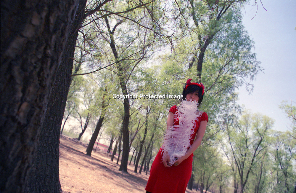 """BEIJING, 24 APRIL 2006: Tian Yuan in the forest.<br /> Tian Yuan is China's latest newcomer in  arts & entertainment . The 21 -year- old came  to fame at the age of 16, when she wrote her first book """" Zebre dans la foret""""which was highly acclaimed in France . Tian is a representative of a """"new generation of young Chinese, born in the mid- eighties,  who for the first time can sing, write…and express themselves… in almost total liberty"""" ( le Monde des livres) .<br /> <br /> Apart from her success as a writer, she's done 4 movies and won a  best newcomer award at the Hongkong film festival for """" Butterfly """" , a movie about a relationship between 2 women . Tian Yuan will travel to the Cannes film festival in May 2006 to promote her new movie """" Luxury Car """" ( director : Wang Chao)"""