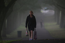 © Licensed to London News Pictures. 15/07/2016. Leeds, UK. A city worker walks through Hyde Park on a foggy autumn morning in Leeds, West Yorkshire. The start of the month has seen temperatures reach the highest they have been in the UK during September since 1911. Photo credit : Ian Hinchliffe/LNP
