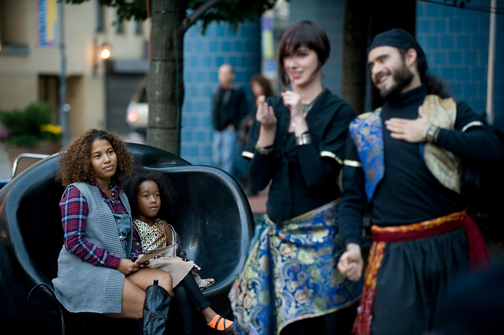 Antoinette Eyth, of Beechview, and daughter Divine Eyth watch Middle Eastern theatrical dance company Moquette Volante perform at Katz Plaza during Pittsburgh Cultural Trust Fall Gallery Crawl in downtown Pittsburgh.