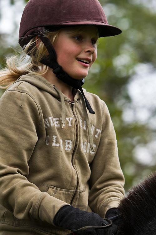 AEROE, DENMARK - 02 OCTOMBER 2010 -- School girls riding horses in a small garden field. PHOTO: ERIK LUNTANG / INSPIRIT Photo...Ridning og spring i frugthaven en soendag eftermiddag. PHOTO: ERIK LUNTANG / INSPIRIT Photo.