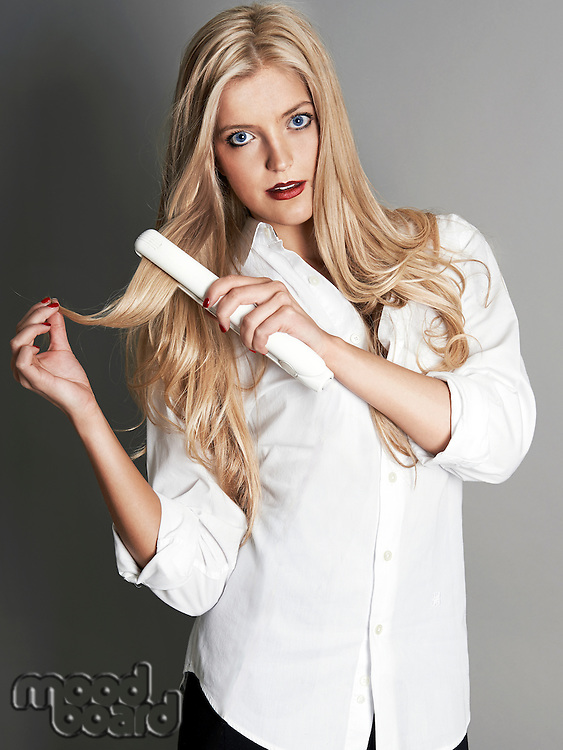Pretty blonde girl with hair straightener