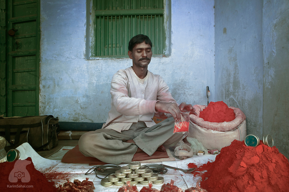 A man packages kumkum into small plastic bags; Pushkar, Rajasthan, India. Kumkum is a saffron or turmeric based powder used as a cosmetic by hindu women. Kumkum is applied as a distinctive dot on the forehead, between the eyebrows.