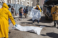 Minister of Health workers prepare  Charite Charle's body, a cholera victim,  found dead next the the National Cathedral in Port-au-Prince, where she lived on the streets with her two children, before taking it away . The Cholera epidemic that started in the north spread to Port-au-Prince.