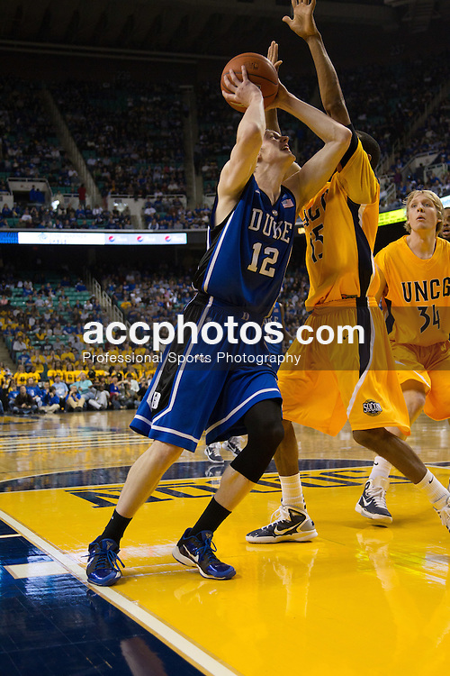 GREENSBORO, NC - DECEMBER 29: Kyle Singler #12 of the Duke Blue Devils drives to the basketball while defended by Trevis Simpson #15 of the UNC-Greensboro Spartans on December 29, 2010 at the Greensboro Coliseum in Greensboro, North Carolina. Duke won 108-62. (Photo by Peyton Williams/Getty Images) *** Local Caption *** Kyle Singler;Josh Hairston