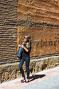 Spanish woman strolling in Calle Sacramento in Leon, Castilla y Leon, Spain