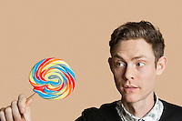 Mid adult man looking at lollipop over colored background