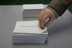 © licensed to London News Pictures. London, UK 06/05/2012. A French national grabbing a voting card before voting at the French Embassy in London for the second round of Presidential Elections, this noon (06/05/12). Photo credit: Tolga Akmen/LNP
