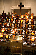 illuminated little votive candles with money collection box and cross