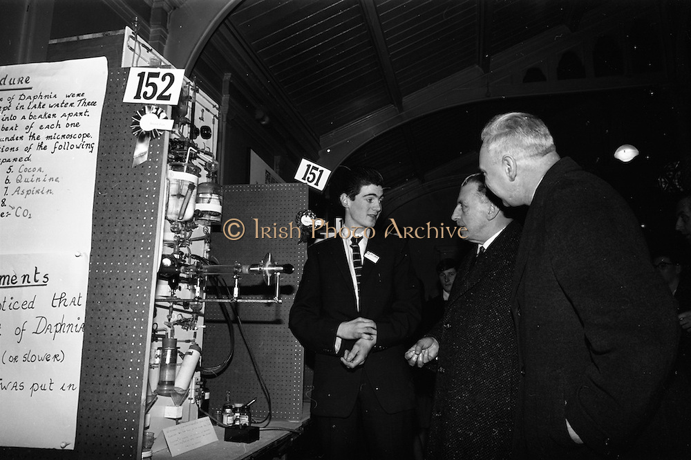 05/01/1965.01/05/1965.5th January 1965.The Aer Lingus Young Scientist Exhibition at the.Manson House..Prize winner Jonh J. Monahan from Newbridge College explains his entry in the Biology Senior section to Taoiseach Sean Lemass and P.J. Lynch, Chairman of Aer Lingus
