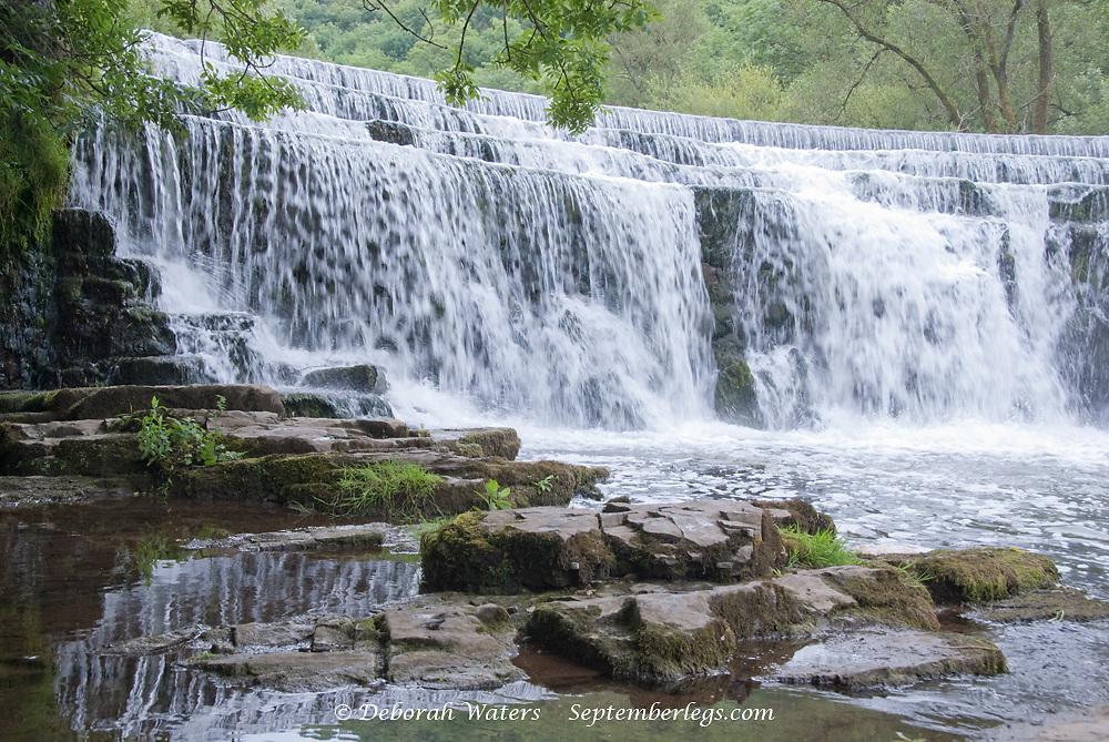 Derbyshire, UK - July 20 2014 - Man made waterfall Monsal Dale weir on the River Wye, Monsal Dale, Derbyshire, Peak District UK