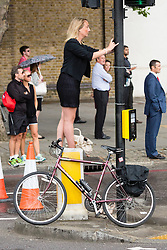 © Licensed to London News Pictures. 07/07/2014. London, UK. A woman finds a vantage point near Tower Bridge ahead of the Tour de France stage 3 in London. Photo credit : Vickie Flores/LNP
