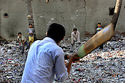 Young resisdents of the Dharavi slum in Bombay take time out to play cricket. The ground is covered with plastic and cloth as Dharavi acts as the recycling area of Bombay particularly in regards to plastic recycling. The slum houses over a million people making it the largest in Asia but it is made the more remarkable by the 5000 one room industries that exist within the slum. This is generating an estimated $800 million to a billion dollars a year. As the price of real estate soars in Bombay and developers move in on the slum the future of Dharavi hangs in the air.