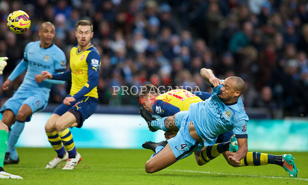 MANCHESTER, ENGLAND - Sunday, January 18, 2015: Manchester City's captain Vincent Kompany tackles Arsenal's Oliver Giroud during the Premier League match at the City of Manchester Stadium. (Pic by David Rawcliffe/Propaganda)