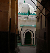Medina, Tangier, Morocco, pictured on December 27, 2009. A view through a narrow street showing the dome above the entrance to a mosque. The building is whitewashed with green decoration. Tangier, the 'White City', gateway to North Africa, a port on the Straits of Gibraltar where the Meditaerranean meets the Atlantic is an ancient city where many cultures, Phoenicians, Berbers, Portuguese and Spaniards have all left their mark. With its medina, palace and position overlooking two seas the city is now being developed as a tourist attraction and modern port. Picture by Manuel Cohen