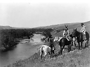 Three Piegan Indians and four horses on hill above river, 1910.    Photograph by Edward Curtis (1868-1952).