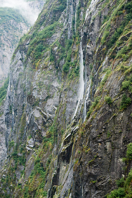 Waterfalls run down the steep, moss-covered cliffs lining the sides of Tracy Arm fjord, Alaska.