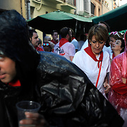 People look for shelter from heavy rain during the first day of the San Fermin Festival on July 6, 2014 in Pamplona, northern Spain. Tens of thousands of people packed Pamplona's streets for a drunken kick-off to Spain's best-known fiesta: the nine-day San Fermin bull-running festival. PHOTO/ RAFA RIVAS