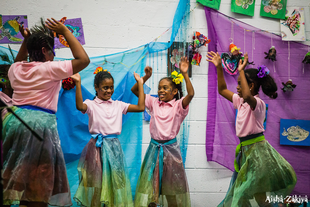 """Students at Gladys Abraham Elementary school perform """"A Blissful Quest for Unity"""" written by art teacher Elise McCutcheon.  Students made their own costumes and set decorations with recycled materials.  Gladys Abraham Elementary school.  26 November 2013.  © Aisha-Zakiya Boyd"""
