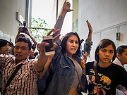 20 NOVEMBER 2014 - BANGKOK, THAILAND: Plainclothes female Thai police officers lead NATCHACAH KONG-UDOM away while arresting her for speaking out against the coup and displaying the three fingered salute from the Hunger Games movies. Kong-Udom was one of at least three people arrested by Thai police during the opening the Hunger Games: Mockingjay - Part 1 in Bangkok Thursday. Opponents of the Thai military coup have adapted the three fingered salute used in the Hunger Games series as a sign of their opposition to the coup. In the weeks before the movie opening Thai police arrested several people for using the Hunger Games salute and Thai media reported that one Thai movie theater chain cancelled plans to show the movie at the request of the military government. There were several small protests at theaters showing the movie Thursday.     PHOTO BY JACK KURTZ