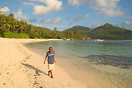 A boy walking on the beach at Baie Lazare<br /> Mahe, The Seychelles<br /> c. Ellen Rooney