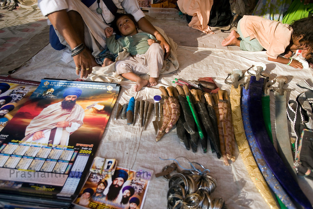 A child of a Nihang or sikh religious soldier sleeps as his father sells swords and knives on the second day of the Khalsa festival celebration in Nanded, 650 kms south of Mumbai on November 2, 2008. Sikhs all over the world are celebrating the 300th year of the consecration of the Sikh holy book, the Guru Granth Sahib. Photographer:Prashanth Vishwanathan