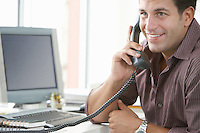 Businessman using telephone at desk in office