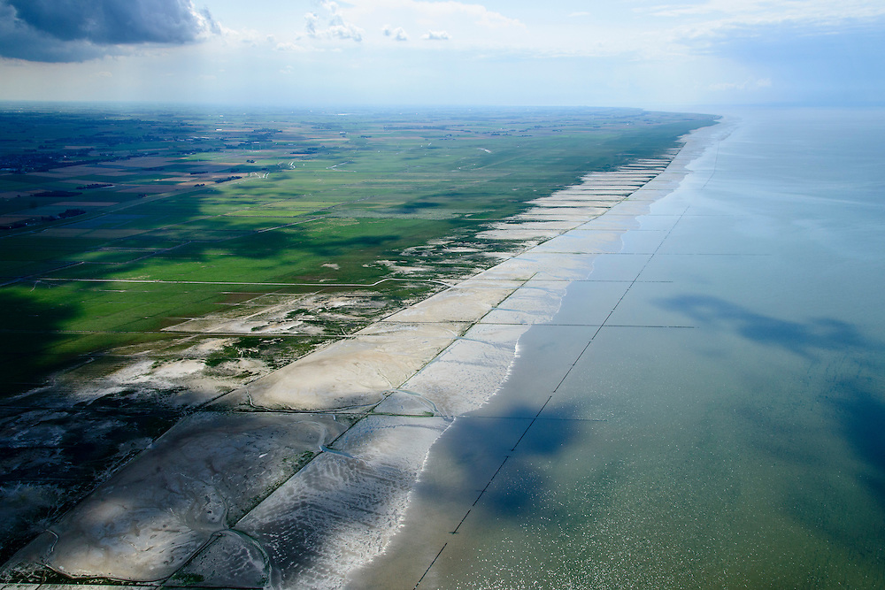 Nederland, Friesland, Gemeente Ferweradeel, 05-08-2014; <br /> Noorderleeg (Noarderleech) ook Noard-Fryslan Butendyks , buitendijkse polder en kweldergebied grenzend aan het Friesche Wad. Landaanwinning door middel van zogenaamde  kwelderwerken. Donkere wolken boven de polders.<br /> <br /> Land reclamation, Noorderleeg (Northern Void), polder and salt marsh area outside the dikes. The so-called salt marsh works consist of square sections, bordered by brushwood breakwaters causing the sludge to settle.<br /> luchtfoto (toeslag); aerial photo (additional fee required); foto Siebe Swart / photo Siebe Swart