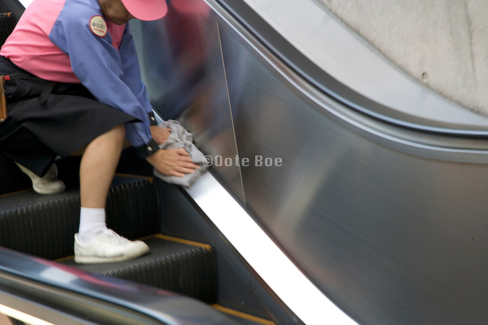 person cleaning a public escalator