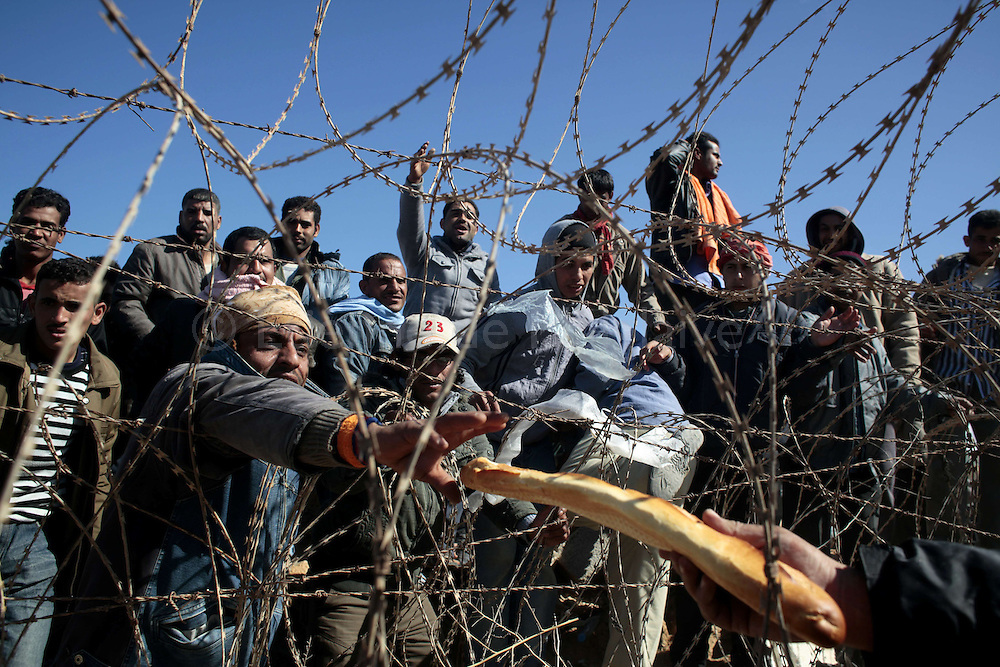 From Tunisia's side, thousand of Egyptians wait on the Libyan side of the border while a Tunisian man toss food and water. March 2012.