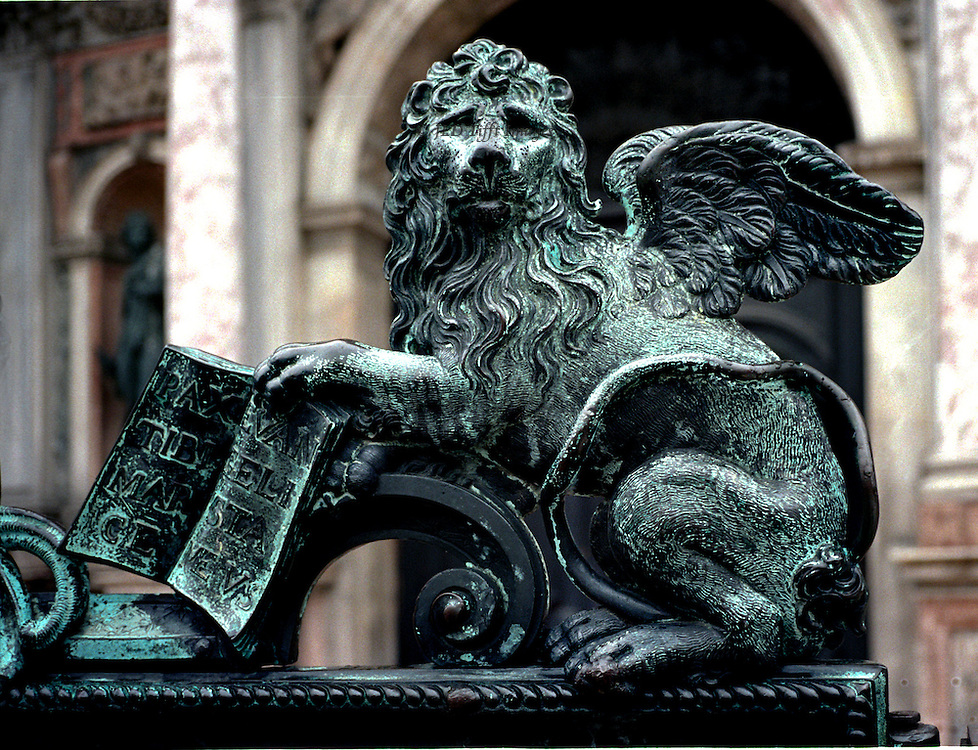Bronze winged lion with book, 18C by Antonio Gai,  on gates to Sansovino's Loggetto, in Piazza of San Marco, Venice.  Detail showing just the lion staring at the camera, holding an open book facing outward.