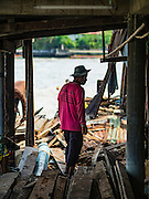 14 OCTOBER 2015 - BANGKOK, THAILAND:  Demolition workers take apart a home on the Chao Phraya River near Wat Kalayanamit. Fifty-four homes around Wat Kalayanamit, a historic Buddhist temple on the Chao Phraya River in the Thonburi section of Bangkok, are being razed and the residents evicted to make way for new development at the temple. The abbot of the temple said he was evicting the residents, who have lived on the temple grounds for generations, because their homes are unsafe and because he wants to improve the temple grounds. The evictions are a part of a Bangkok trend, especially along the Chao Phraya River and BTS light rail lines. Low income people are being evicted from their long time homes to make way for urban renewal.         PHOTO BY JACK KURTZ