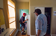 Michael Cumberledge, Jr. of Insulation Concepts checks above and behind a refridgerator for air movement, as Tom Calhoun looks on, during an energy audit at 47 West Washington Street on Tuesday, June 23, 2015.  Photo by Ohio University  /  Rob Hardin