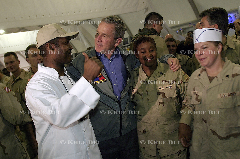 Pres. Bush spends Thanksgiving dinner with troops of the 1st Armor Division in a mess hall at Baghdad International Airport Thursday, November 27, 2003.  In a clandestine night time move President Bush, with the knowledge of only a handful of senior staff, departed his ranch in Crawford, Texas and flew through the night to spend the Thanksgiving Day holiday visiting troops stationed in the war torn country...Photo by Khue Bui
