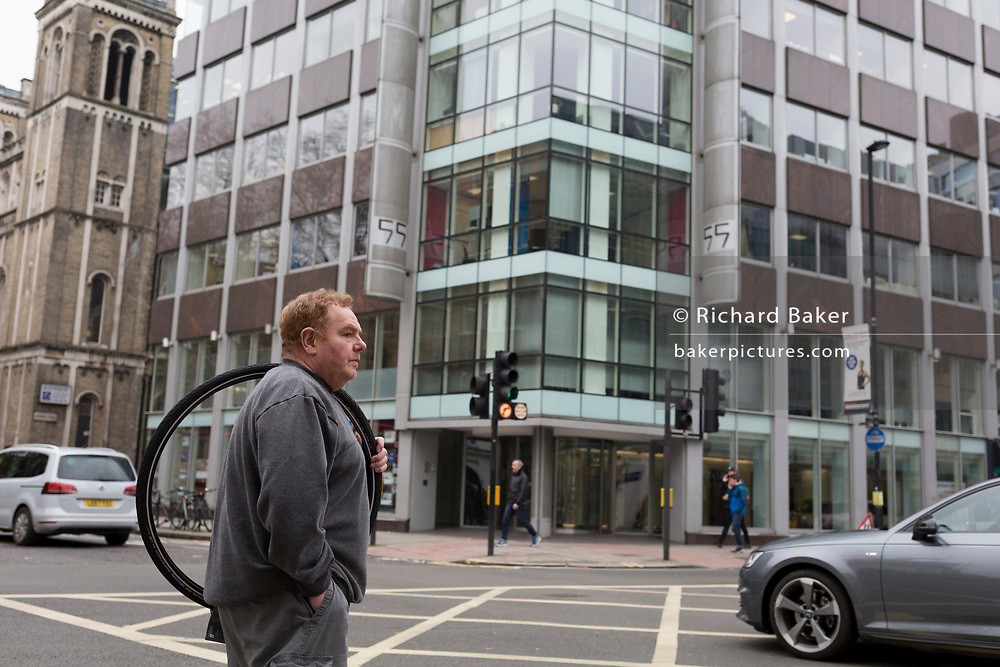 The day after Facebook's Mark Zuckerberg faced Senate Committee questions in Washington, a man carries a spare bicycle wheel acorss New Oxford Street outside the offices of Cambridge Analytica, the UK tech company accused of harvesting the personal details of Facebook users (including Zuckerberg himself) in its data privacy scandal, on 11th April, 2018, in London, England.