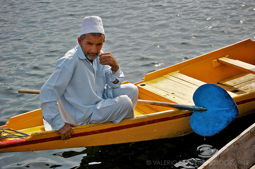 A Kashmiri man and his canoe. Dal Lake, Srinagar<br /> Kashmir. India.
