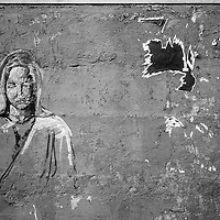Where: Cuzco, Peru.<br /> I have various shots of this wall graffiti. I like this one with the Cement line at the top of the image. I feel it 'grounds' the image. Also the message from the scratched lady and the torn poster sends a profound message.