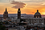 Sunset over the iconic churches in the historic center of San Miguel de Allende, Guanajuato, Mexico. The Parroquia de San Miguel Arcangel, left, San Francisco church, right.