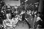 "18/12/1962<br /> 12/18/1962<br /> 18 December 1962<br /> Draw for four large Christmas hampers at Todco, Dublin. Picture shows ""General"" Charlie Byrne drawing one of the lucky numbers watched by a large crowd of customers."