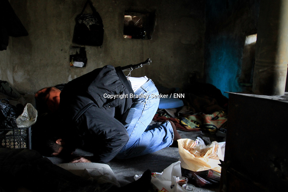 A soldier from the Free Syrian Army prays in a farmhouse used as a temporary military base in the farmland surrounding Al Janoudiyah, Syria.