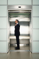 Businessman Straightening Tie in Elevator side view