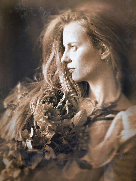 A woman seated, with long loose blond hair and a thoughtful expression, holding a bunch of flowers.