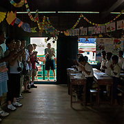 """Tourists on a guided tour of Chong Kneas, the poverty-striken floating village just outside of Siem Reap, Cambodia, clap after fourth grade students sing them a """"Welcome Song"""" and the National Anthem."""