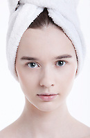 Portrait of young woman with towel wrapped around her head against white background