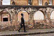 A Mexican man dressed as the Dapper Skeleton walks past the Templo del Sagrario during the Day of the Dead or Día de Muertos festival October 31, 2017 in Patzcuaro, Michoacan, Mexico. The festival has been celebrated since the Aztec empire celebrates ancestors and deceased loved ones.